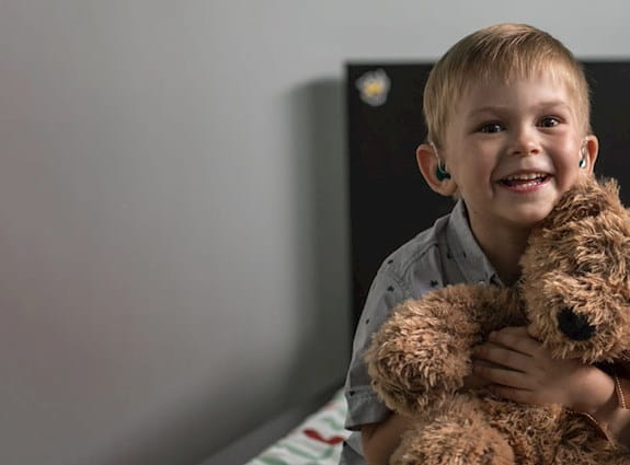 Young boy holding a brown teddy bear, sitting on his bed, smiling