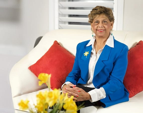 Woman with short, brown hair, sitting on a couch, wearing a blue blazer, yellow daffodil pin, white collared shirt, smiling