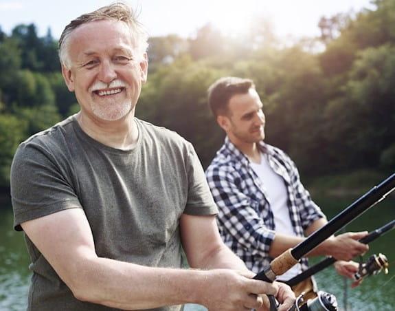 Older man, facing forward, smiling with younger man, fishing.